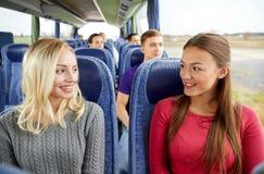 Mujeres jovenes felices que hablan en autobús del viaje Imagenes de archivo