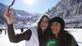 Mujeres jovenes felices que hacen el selfie por el teléfono móvil, muchachas divertidas del patinaje de hielo almacen de metraje de vídeo