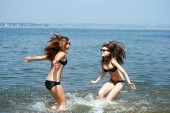 Mujeres jovenes felices que juegan en la playa Foto de archivo
