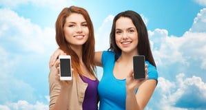 Mujeres jovenes felices que muestran las pantallas de los smartphones Fotos de archivo libres de regalías