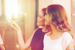 Mujeres jovenes felices que señalan el finger a la ventana de la tienda Imagen de archivo libre de regalías