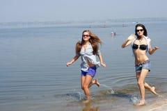 Mujeres jovenes felices que se ejecutan a través de la playa Foto de archivo