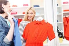 Mujeres jovenes felices que soportan los vestidos en tienda Fotografía de archivo libre de regalías