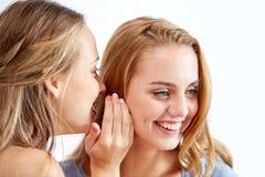 Mujeres jovenes felices que susurran chisme en casa Foto de archivo