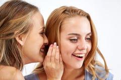 Mujeres jovenes felices que susurran chisme en casa Imágenes de archivo libres de regalías