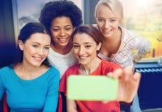 Mujeres jovenes felices que toman el selfie con smartphone Fotografía de archivo