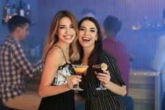 Mujeres jovenes hermosas con los c?cteles de martini fotografía de archivo libre de regalías
