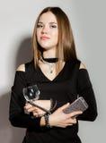 Mujeres jovenes hermosas del negocio de moda en un poco vestido negro con los accesorios, sosteniendo el teléfono y la copa de vi Foto de archivo libre de regalías
