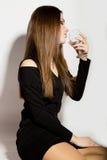 Mujeres jovenes hermosas del negocio de moda en un poco vestido negro con los accesorios, sosteniendo una copa de vino vacía Imágenes de archivo libres de regalías