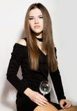 Mujeres jovenes hermosas del negocio de moda en un poco vestido negro con los accesorios, sosteniendo una copa de vino vacía Fotos de archivo libres de regalías