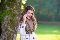 Mujeres jovenes hermosas en el parque usando un teléfono celular Fotografía de archivo