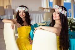 Mujeres jovenes hermosas en un día de verano damas de honor en vestidos amarillos en un restaurante del mar Imagenes de archivo