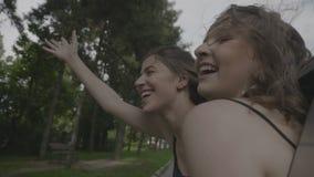 Mujeres jovenes hermosas exuberantes inclinadas fuera del coche de la ventana que disfruta del viaje que ríe y que gesticula viaj almacen de metraje de vídeo