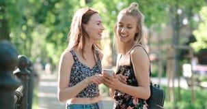 Mujeres jovenes hermosas que miran las fotos en un teléfono Fotos de archivo libres de regalías