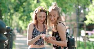Mujeres jovenes hermosas que miran las fotos en un teléfono Foto de archivo