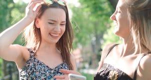 Mujeres jovenes hermosas que miran las fotos en un teléfono Fotos de archivo