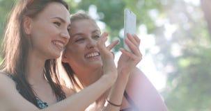 Mujeres jovenes hermosas que miran las fotos en un teléfono Imagen de archivo
