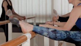 Mujeres jovenes hermosas que realizan las fracturas que estiran en el cuarto del ensayo Las muchachas delgadas se colocan delante metrajes