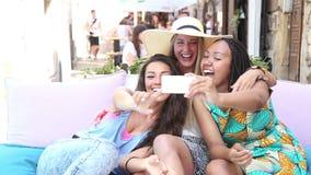 Mujeres jovenes hermosas que se divierten que toma selfies en ciudad almacen de video