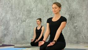 Mujeres jovenes hermosas que se resuelven en el desván interior, haciendo el ejercicio de la yoga, sentándose en el asana fácil p fotografía de archivo