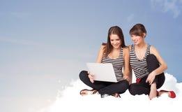 Mujeres jovenes que se sientan en la nube con el espacio de la copia Foto de archivo libre de regalías