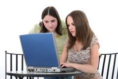 Mujeres jovenes hermosas que trabajan junto en la computadora portátil Fotografía de archivo libre de regalías