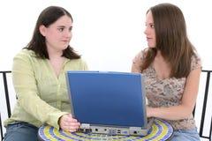 Mujeres jovenes hermosas que trabajan junto en la computadora portátil Fotografía de archivo