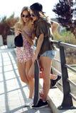 Mujeres jovenes hermosas que usan el teléfono móvil en la calle Fotografía de archivo
