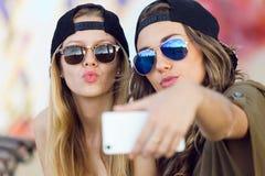 Mujeres jovenes hermosas que usan el teléfono móvil en la calle Imagenes de archivo