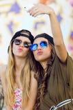 Mujeres jovenes hermosas que usan el teléfono móvil en la calle Foto de archivo libre de regalías