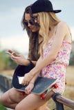 Mujeres jovenes hermosas que usan el teléfono móvil en la calle Imagen de archivo libre de regalías