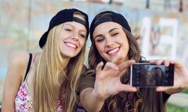 Mujeres jovenes hermosas que usan el teléfono móvil en la calle Imagen de archivo