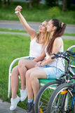 Mujeres jovenes lindas del motorista que toman el autorretrato en parque Foto de archivo