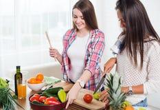 Mujeres jovenes magníficas que preparan la cena en una cocina Imagen de archivo