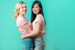 Mujeres jovenes multiétnicas que abrazan en el fondo azul del estudio con el espacio de la copia Fotos de archivo