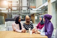 Mujeres jovenes musulmanes de la pertenencia ?tnica diversa que hablan del nuevo libro del autor famoso fotos de archivo libres de regalías