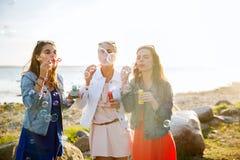 Mujeres jovenes o muchachas que soplan burbujas en la playa Imágenes de archivo libres de regalías
