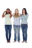 Mujeres jovenes que actúan hacia fuera tres monos sabios Imagen de archivo libre de regalías