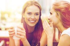 Mujeres jovenes que beben el café y que hablan en el café Imágenes de archivo libres de regalías