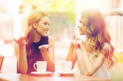 Mujeres jovenes que beben el café y que hablan en el café Imagenes de archivo