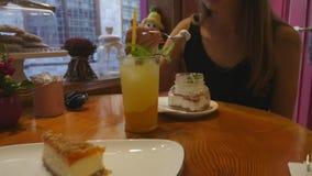 Mujeres jovenes que beben la limonada y que comen las tortas en el caf? metrajes