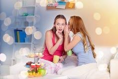 Mujeres jovenes que beben té y que cotillean en casa Fotografía de archivo