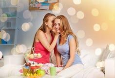 Mujeres jovenes que beben té y que cotillean en casa Fotos de archivo libres de regalías
