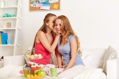 Mujeres jovenes que beben té y que cotillean en casa Fotografía de archivo libre de regalías