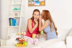 Mujeres jovenes que beben té y que cotillean en casa Imagenes de archivo