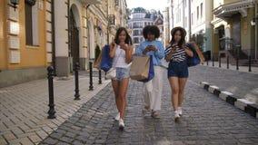 Mujeres jovenes que caminan con los teléfonos y los panieres metrajes