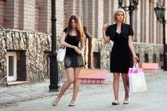 Mujeres jovenes que caminan en una calle de la ciudad Foto de archivo libre de regalías