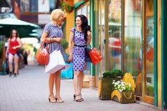 Mujeres jovenes que caminan las tiendas de la ciudad, haciendo compras Foto de archivo libre de regalías