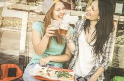 Mujeres jovenes que comen la pizza y que beben la cerveza en el restaurante de la barra Fotografía de archivo