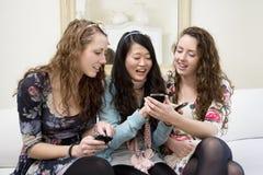 Mujeres jovenes que comparten el vídeo en el teléfono celular Imagen de archivo libre de regalías